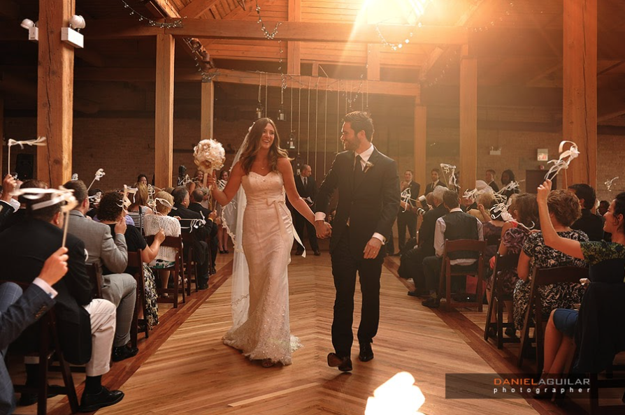 A bride and groom walk down the aisle celebrating after getting married.