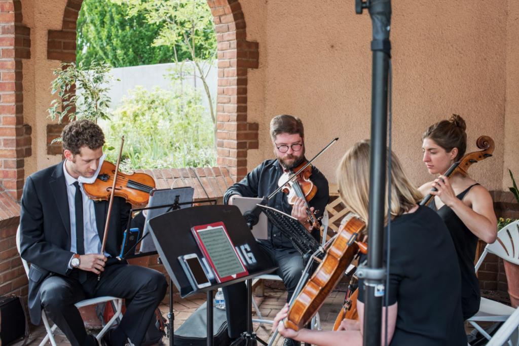 A string quartet plays a custom playlist during a wedding prelude.