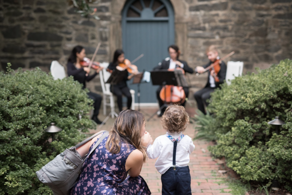 A wedding guest and her toddler son relax next to the wedding string quartet as they play a custom playlist during a wedding prelude.